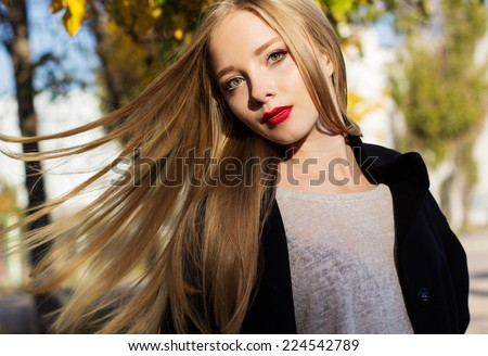 Pretty girl with flying hairs in colorful leaves - stock photo