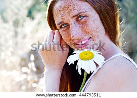 Pretty girl with freckles relaxing outdoor on sunset. Woman with a bouquet of daisies - stock photo