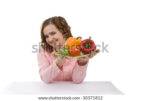 Pretty girl with fresh vegetables.  Housewife is holding the plate with pepper, tomato, cucumber.  Isolated over white background. - stock photo