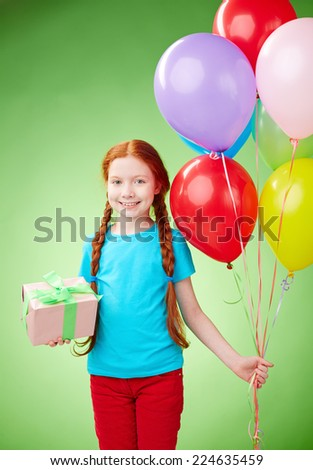 Pretty girl with giftbox and balloons having birthday - stock photo