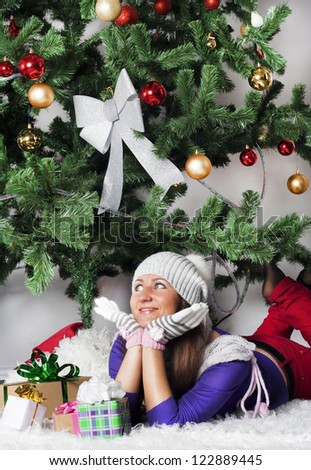Pretty girl with gifts beside green Christmas Tree - stock photo