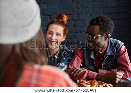 Pretty girl with ginger hair and African hipster in glasses having fun, laughing during lunch at cafe, enjoying lively conversation with their old female friend who is sitting with her back to camera