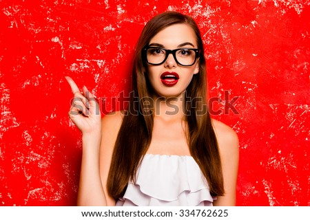 Pretty girl with glasses pointing away against the red background - stock photo