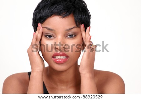 Pretty girl with headache and stress grimacing and holding head - stock photo
