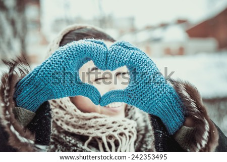 Pretty girl with heart shaped hands is the gloves outdoor - stock photo