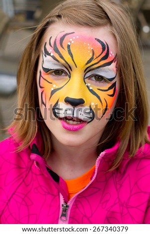 Pretty girl with her face painted as a tiger - stock photo