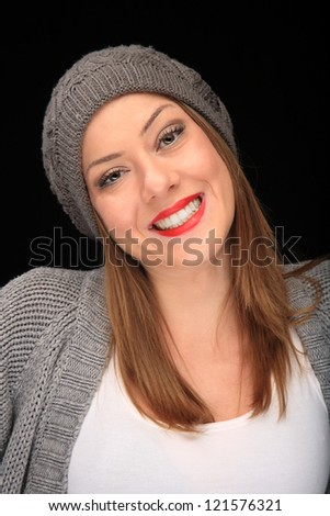 pretty girl with knit top and grey cap on a black background