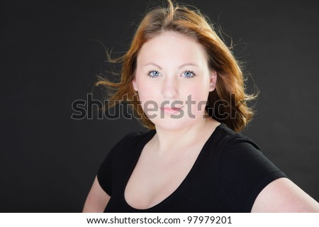 Pretty girl with long brown hair isolated on dark background. Studio portrait.