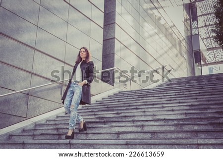 Pretty girl with long hair poses in the city streets - stock photo