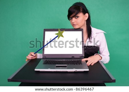 Pretty girl with magic wand and laptop with blank screen. - stock photo