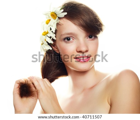 pretty girl with many camomile flowers against white background
