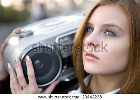 Pretty girl with MP3 stereo system on the street background