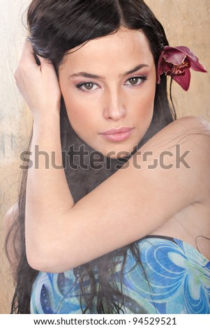 Pretty girl with red orchid in her hair in vapor environment