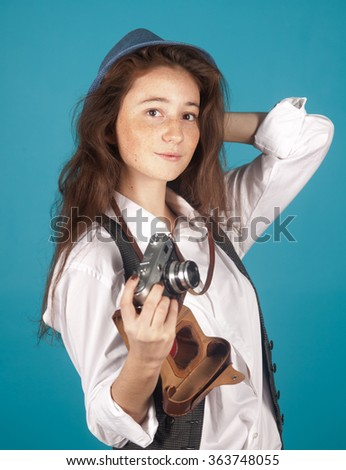 pretty girl with retro camera in hands on a blue background