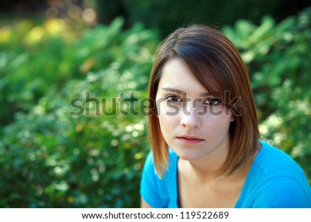 pretty girl with short hair sitting outside - stock photo
