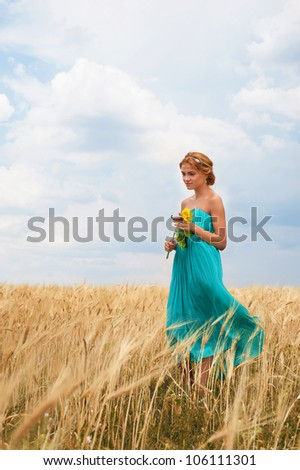 Pretty girl with sunflower in her hands walking through the wheat field - stock photo