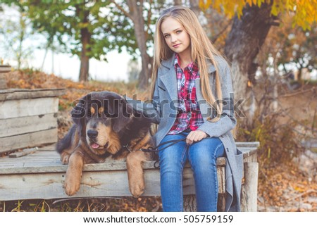 Pretty girl with tibetan mastiff on the nature