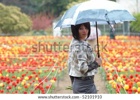 Pretty girl with umbrella in the garden - stock photo