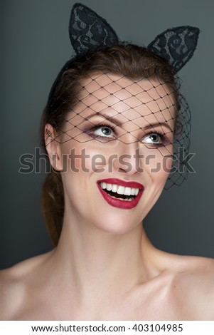 Pretty girl with unusual hairstyle, bright makeup, red lips and manicure. Beauty face. Art accessory. Studio portrait - stock photo