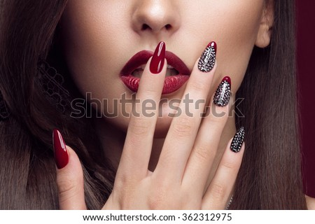 Pretty girl with unusual hairstyle, bright makeup, red lips and manicure design. Beauty face. Art nails. Studio portrait - stock photo