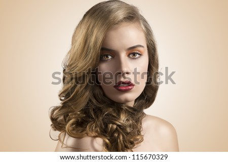 pretty girl with wavy hair and red lipstick, she is in front of the camera and looks in to the lens - stock photo
