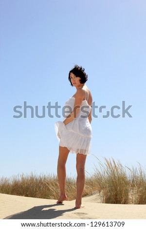 pretty girl with white dress walking on the sand - stock photo