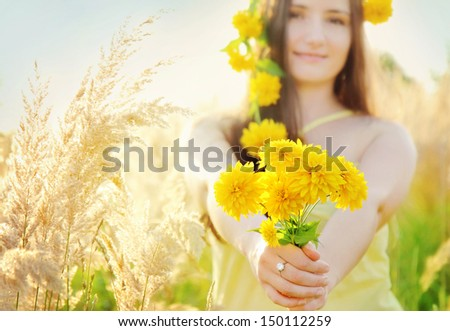 Pretty girl with yellow flowers crown in the grassy sunny summer field holding bouquet - stock photo