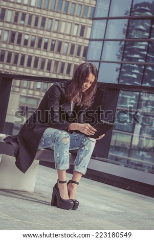 Pretty girl works with her tablet in the city streets