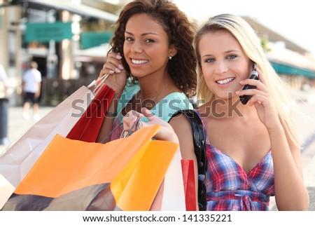 Pretty girlfriends doing shopping - stock photo