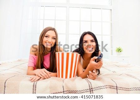 Pretty girlfriends lying on bed with popcorn and watching interesting film