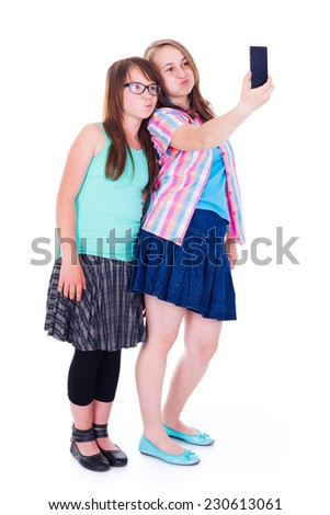 Pretty girlfriends standing and taking a selfie with mobile phone - stock photo