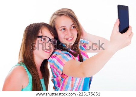Pretty girlfriends taking selfie with mobile phone - stock photo