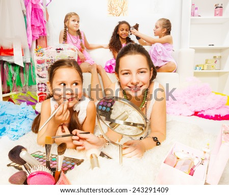 Pretty girls applying make-up with friends behind - stock photo