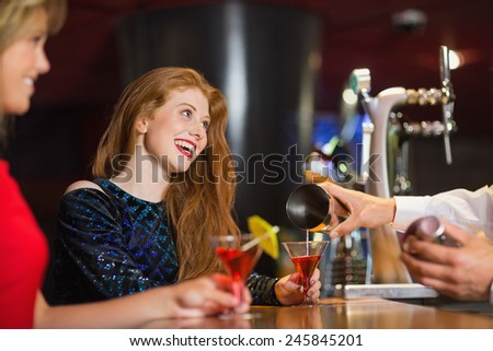 Pretty girls being served cocktails in a bar - stock photo