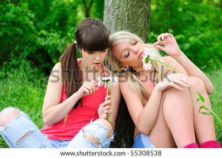 pretty girls fortune-telling on camomiles - stock photo