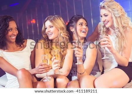 Pretty girls holding champagne glass in a nightclub - stock photo