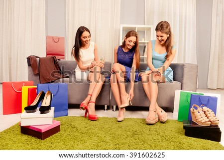 Pretty girls looking at new shoes of their sister - stock photo