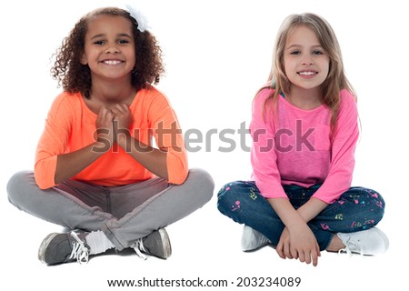 Pretty girls sitting on the floor and playing - stock photo