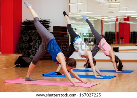 Pretty girls trying to do a standing split during their yoga class in a gym - stock photo
