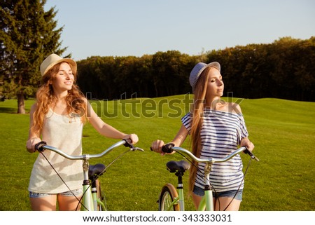 pretty girls with a hats enjoying the sun with a bicycle - stock photo