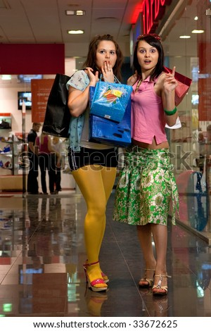 Pretty girls with colorful bags in the shop - stock photo