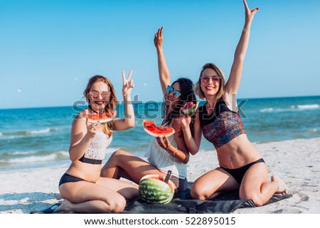 Pretty girls with watermelon on the beach. Summertime concept.