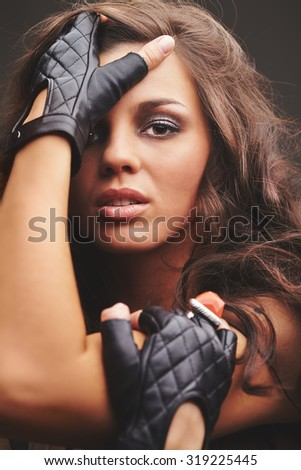 Pretty glam rock girl in black leather gloves looking at camera