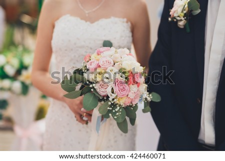 Pretty good wedding bouquet of various flowers in hand