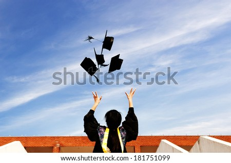 pretty graduate throwing graduation hats in the air. - stock photo