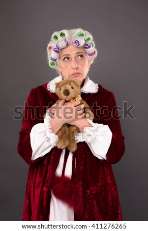 Pretty grandmother posing with teddy bear over grey background having nostalgia about old times in her childhood. - stock photo