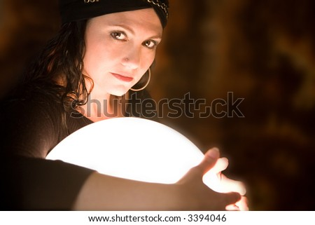 Pretty gypsy woman protectively holding her arms around her crystal ball - stock photo