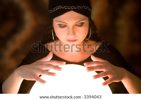 Pretty gypsy woman with her hands above her crystal ball predicting the future - stock photo