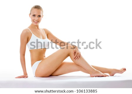 Pretty half-dressed woman sitting on a white background - stock photo