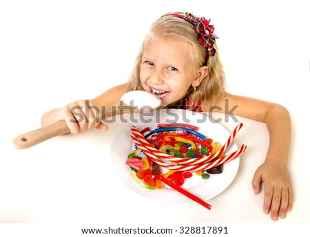 pretty happy Caucasian female child eating dish full of candy holding sugar spoon in sweet caramel abuse dangerous diet and unhealthy nutrition concept isolated on white background - stock photo